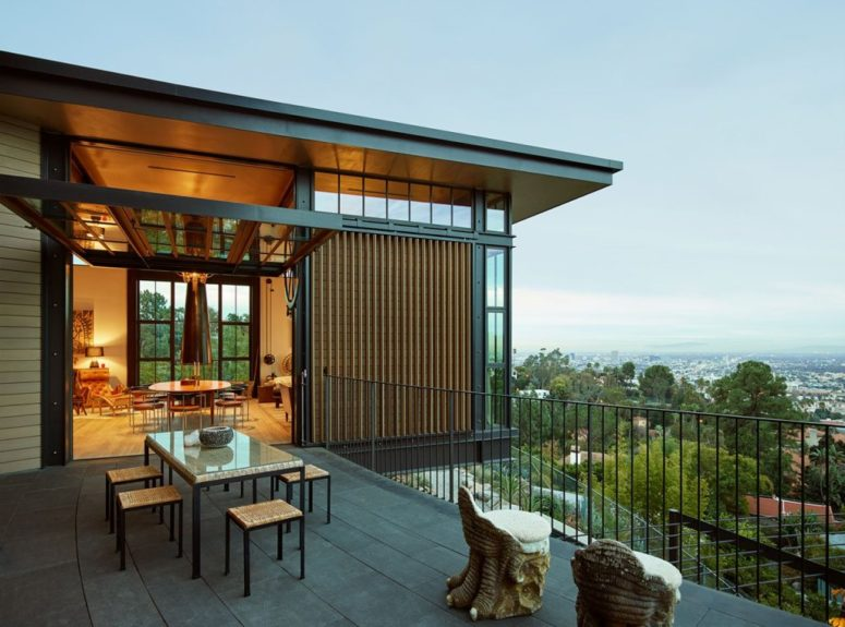 This outdoor space is a dining zone with wicker furniture and whimsical chairs
