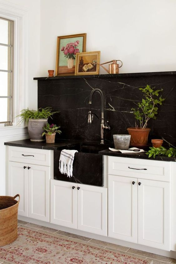 a neutral farmhouse kitchen with a black marble backsplash and coutnertops plus a black built-in sink