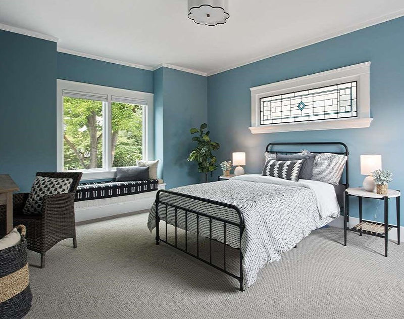 A guest bedroom is done in blue, with several windows, comfy metal and wicker furniture and monochromatic textiles