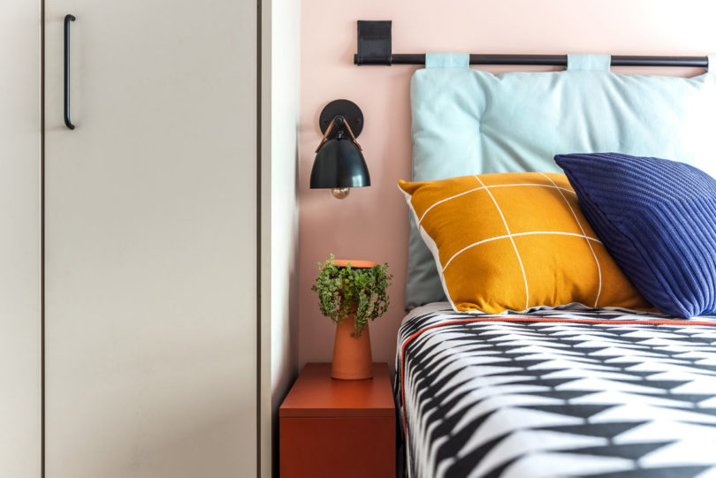 The bedroom also shows off bright colors and prints and matte black touches add drama here