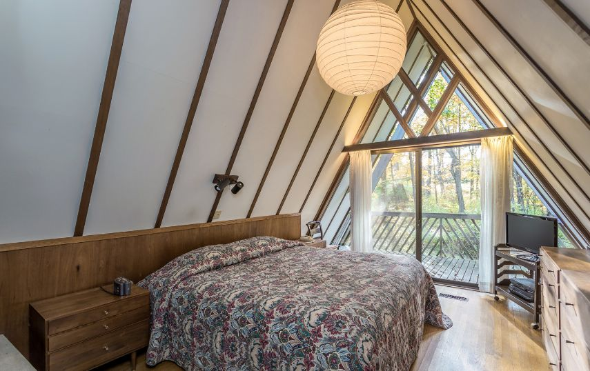 This bedroom also features a glass wall, some comfy furniture and cozy light