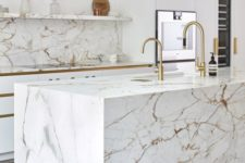 09 a modern luxurious kitchen with white cabinets, a white marble kitchen island and a backsplash plus gold fixtures