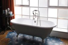 09 a stylish bathroom with a wooden floor and a blue hex tile with stars floor piece under the tub is gorgeous