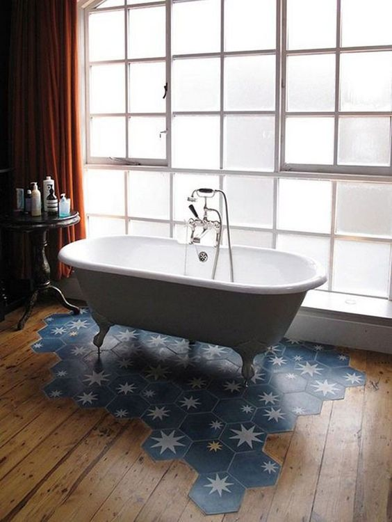a stylish bathroom with a wooden floor and a blue hex tile with stars floor piece under the tub is gorgeous