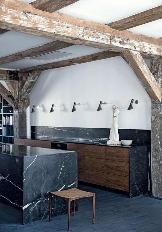 a stylish kitchen with a black marble backsplash and countertops and a matching kitchen island looks cool