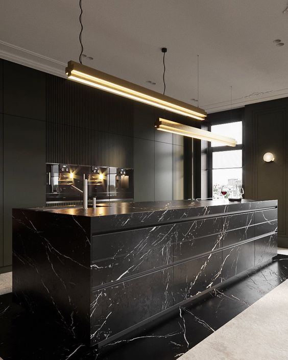 an exquisite black kitchen with plain cabinets and an oversized black marble kitchen island plus touches of gold