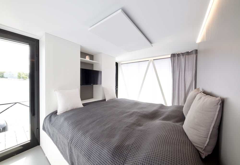 The bedroom features a comfy bed, glazings and a built in TV on the wall
