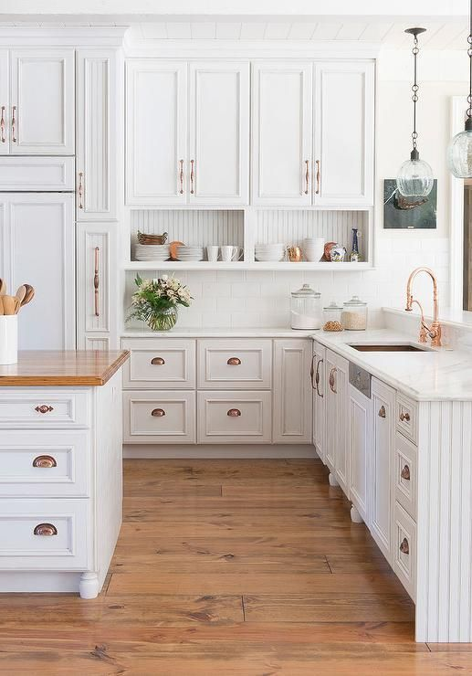 a vintage white kitchen accented with copper hardware to give more color and chic to the space
