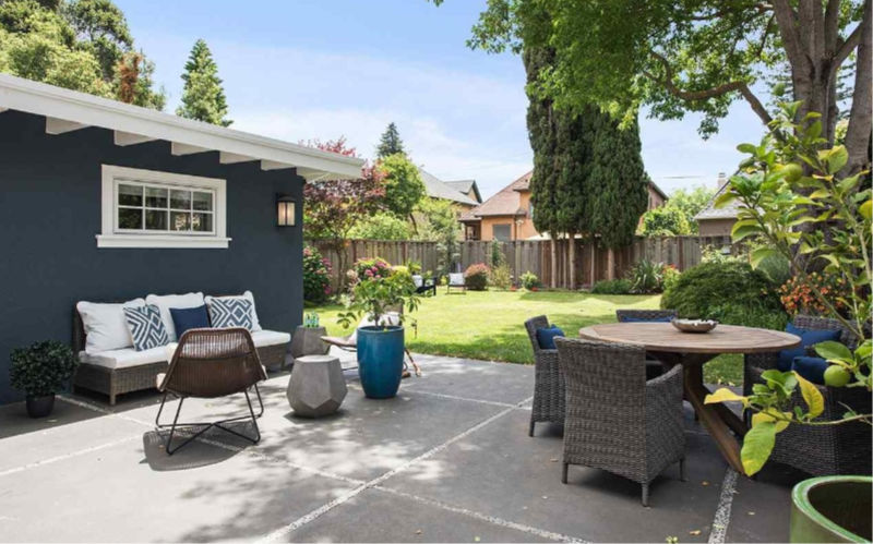 The backyard features a lawn and a dining and living space with stylish furniture and potted plants