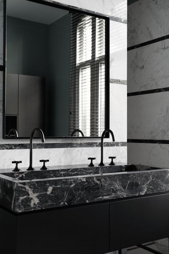 a modern moody bathroom with a black marble sink for a refined touch and black matte fixtures for a chic look
