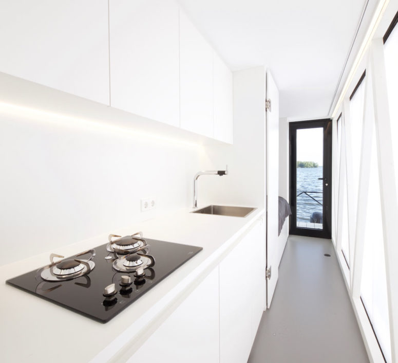 A kitchen is also present, it's done in white, with built-in lights and a comfy surface for cooking