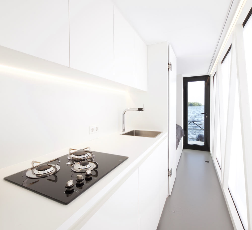 A kitchen is also present, it's done in white, with built in lights and a comfy surface for cooking
