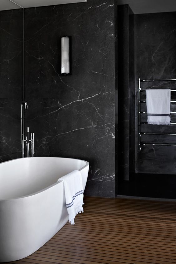 a contemporary bathroom with black marble walls, a wooden slab floor and neutral appliances for a chic look