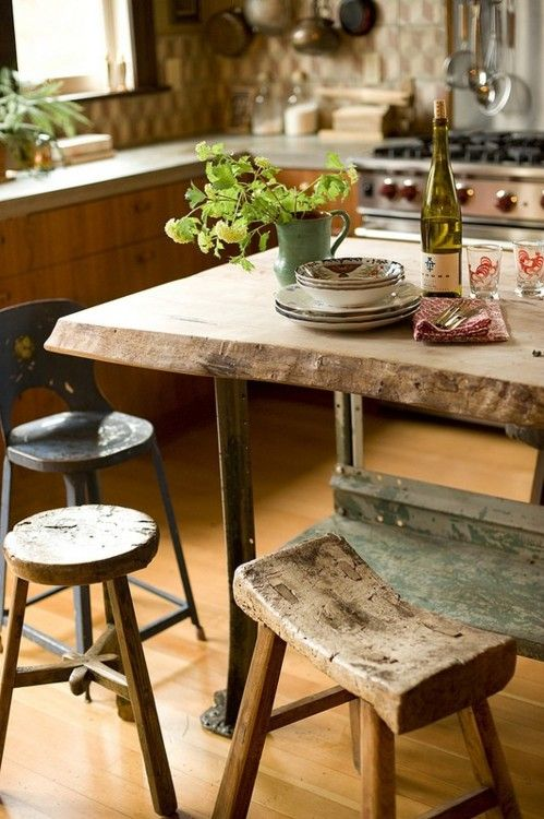 a rough wooden table and kitchen island, with mix and match wooden stools looks very rustic