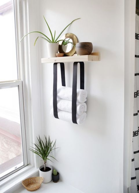 a wood and leather strap towel shelf will let you store not only towels but also decor and accessories