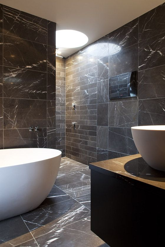 a chic minimalist bathroom clad with blakc marble tiles of various sizes and shapes plus white appliances for a contrast