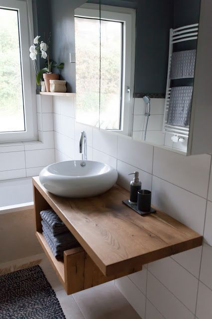 a modern wooden vanity with an open storage space that allows to store some towels is a cool idea