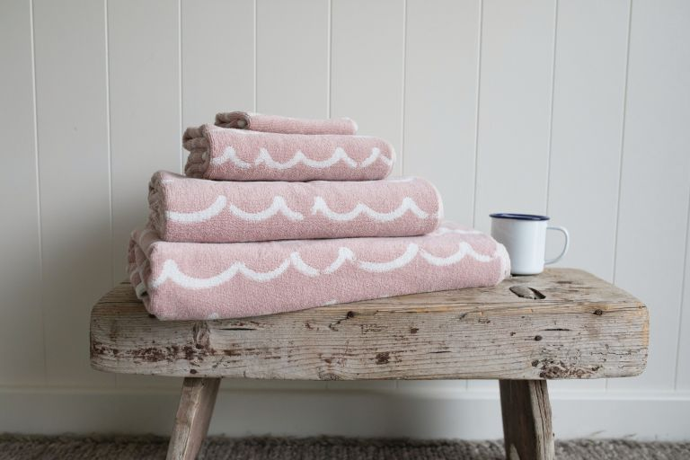 a rustic side table or bench will always add a natural touch to the space and you can store towels on it