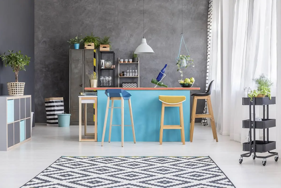 a small bright kitchen with a blue kitchen island and a set of mismatching colorful stools