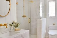 16 a chic and glam white bathroom with white tiles, a white marble floating sink and touches of gold for a shiny look
