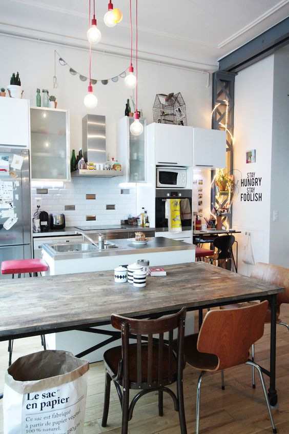 a quirky kitchen with a wooden table and al mismatching chairs and stools at the tables