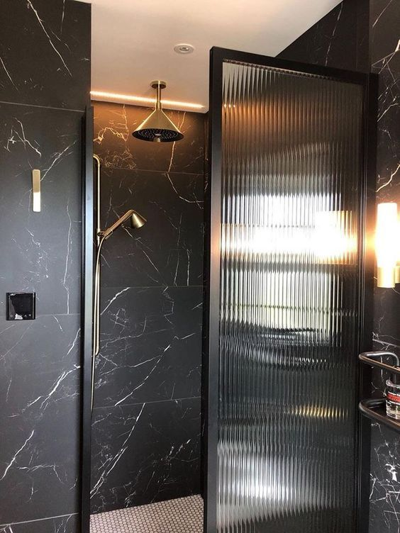 a refined modern bathroom clad with black marble tiles, with built in lights and matte black touches