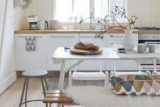 17 a Scandinavian kitchen with a white dining table and mismatching benches, chairs and stools