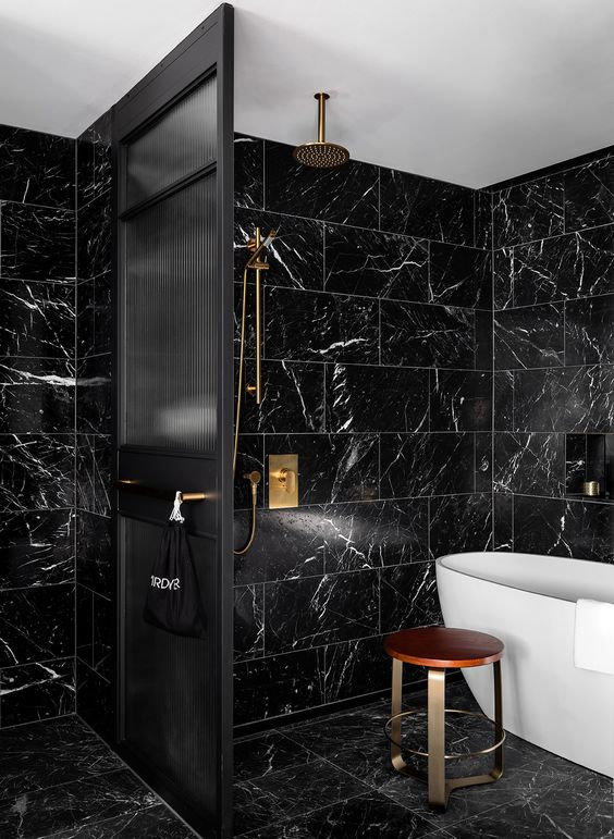 a stylish black bathroom clad with marble tiles, with a white tub for a contrast and brass touches