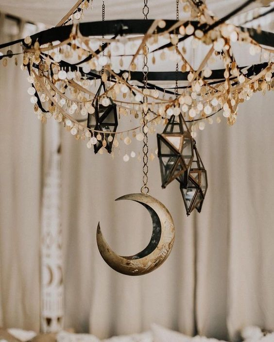 a chandelier with coins, 3D star candleholders and a moon will make your space very boho and celestial