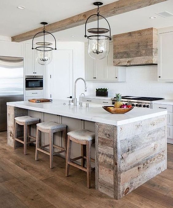 a neutral modern farmhouse kitchen with statement glass and metal lights over the kitchen island