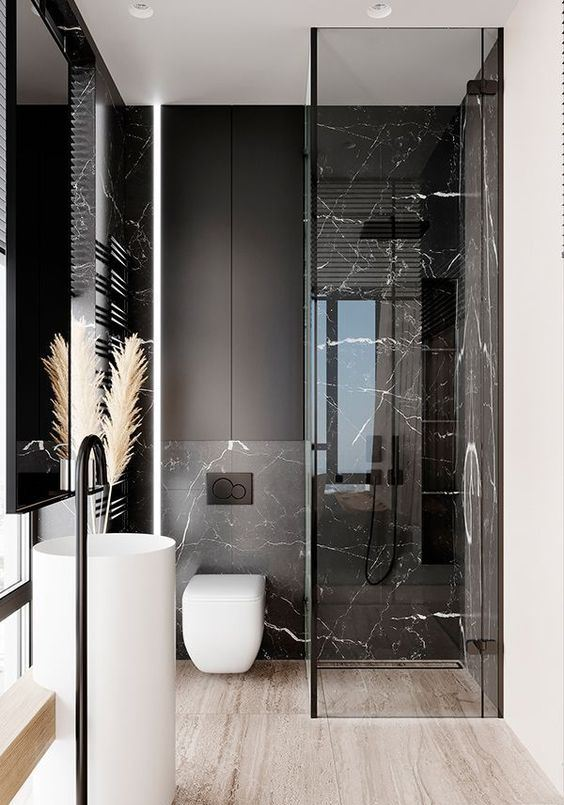 a refined minimalist bathroom with black marble tiles, black matte surfaces and white appliances for a bold look