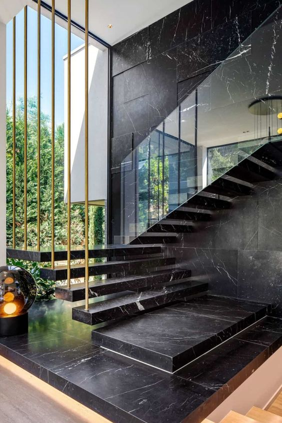 a black marble wall and a matching floating staircase make the layout luxurious and very chic