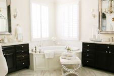 19 a refined white bathroom with a white marble floor, black furniture, a crystal chandelier and statement mirrors