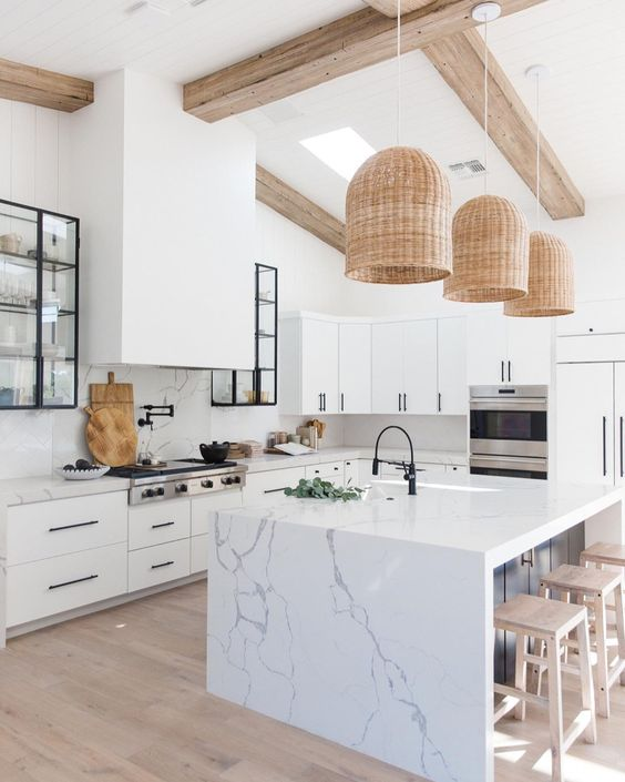 statement wicker pendant lamps over the kitchen island give a cozy and welcoming feel to the space
