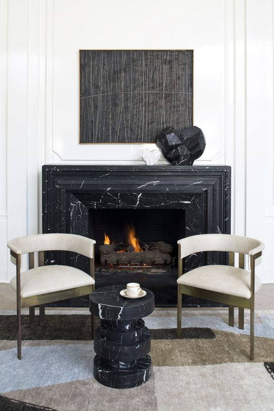 a catchy fireplace nook with a black marble clad fireplace, refined chairs and a black marble side table
