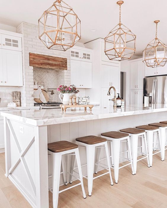 a white farmhouse kitchen with vintage gold faceted pendant lamps over the kitchen island