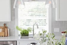 21 neutral and modern glass pendant lamps over the kitchen island and cabinets give style to the space