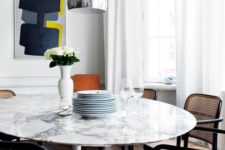 22 a chic white marble round dining table and rattan and cane chairs make up a chic mid-century modern dining zone