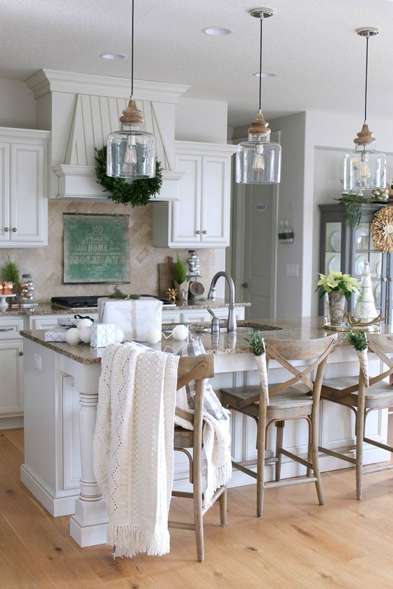 a cozy farmhouse kitchen with a row of glass and wood pendant lamps over the kitchen island