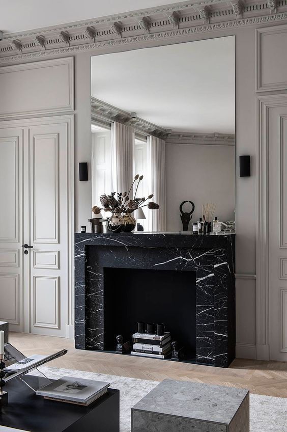 a refined living room with a large non-working fireplace clad with black marble for a chic touch