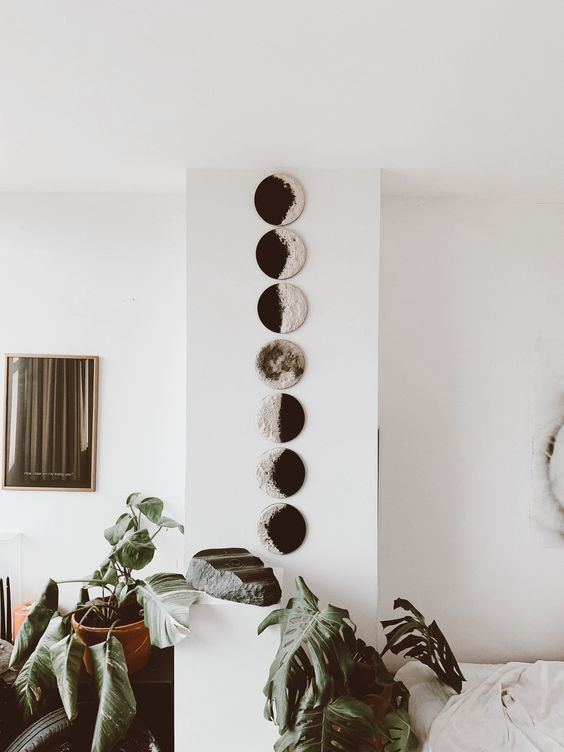 a wall art with moon phases is very lovely and looks modern and bold, perfect for a boho space