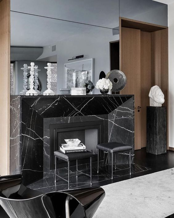 a refined space with a black marble fireplace, black leather sotols and a large mirror is wow