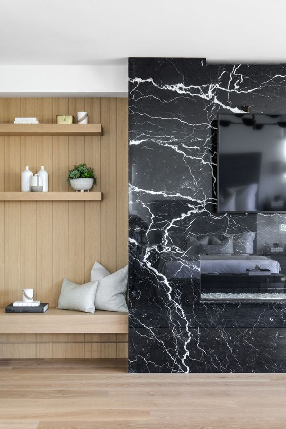 a TV and a built in fireplace on a black marble panel look super chic and refined