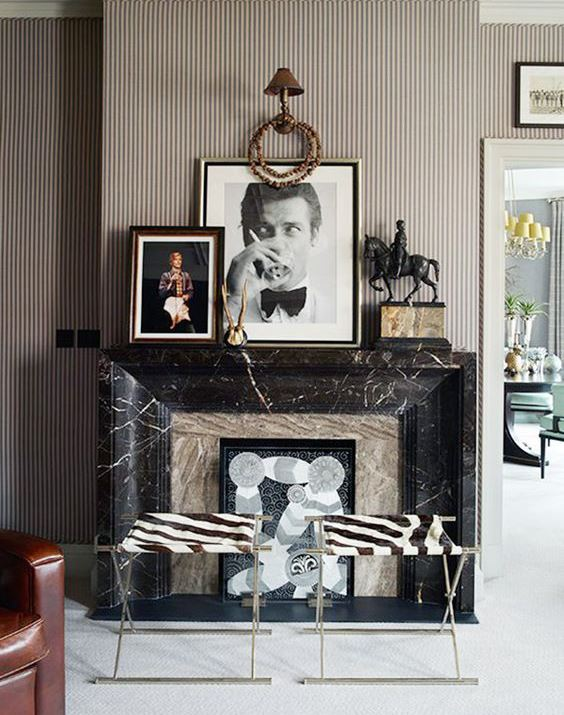 a whimsical fireplace clad with neutral stone and black marble plus artworks and animal print stools