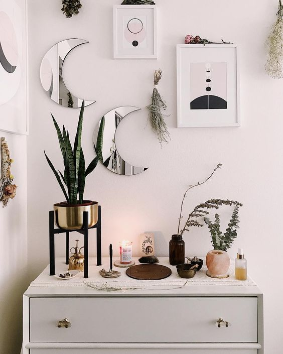 mini moon mirrors and abstract artworks plus herbs look cool and bring a romantic celestial feel to the space