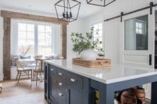 26 a navy kitchen island that includes an open storage space and some drawers, too