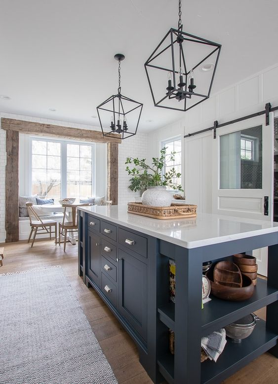 a navy kitchen island that includes an open storage space and some drawers, too