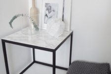 26 a side table with a black metal base and a white marble countertop – if you can't afford marble, go for contact paper