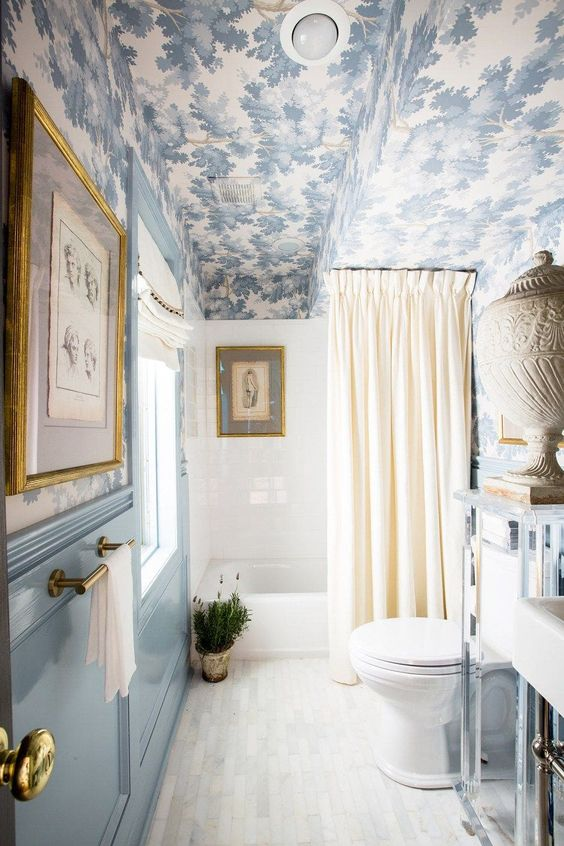 a beautiful vintage-inspired blue and white bathroom with a printed wallpaper ceiling echoing the colors below
