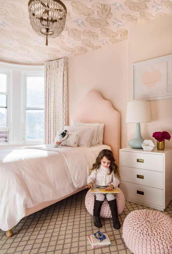 a blush girl's bedroom accented with printed wallpaper on the ceiling looks more interesting and dreamy